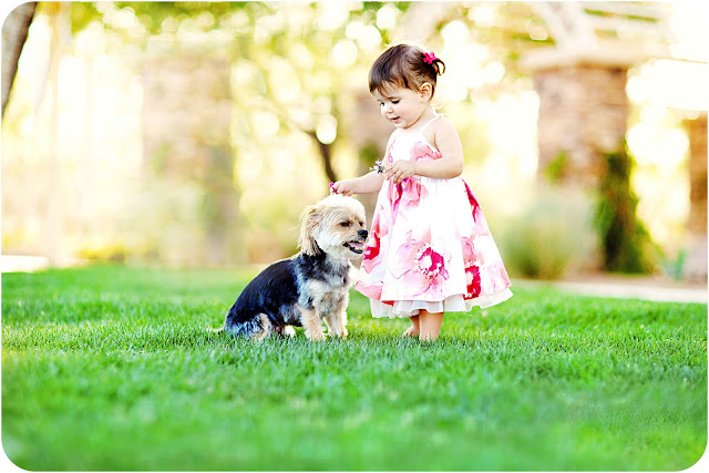 Photograph of a toddler girl with her dog