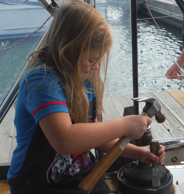 Chasity helping to chisel the corrosion out from between the aluminum base and bronze winch
