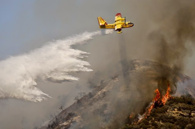 Plane drops fire suppression chemicals. (Credit: AP/Jae C. Hong) Click to enlarge.