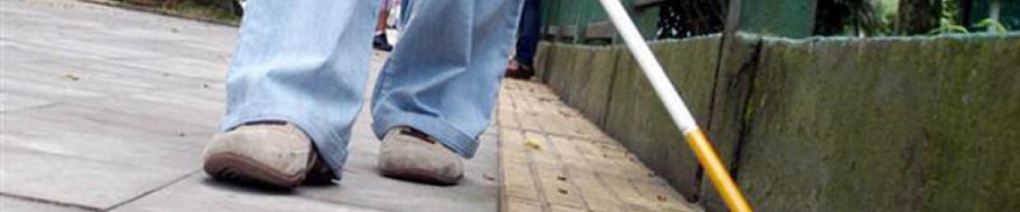 Pernas de uma pessoa caminhando e usando bengala guia