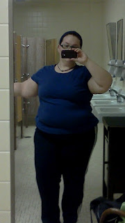 Author with hair pulled back in ponytail with navy headband, blue fitted tshirt, with navy blue trackpants with white stripes on the side