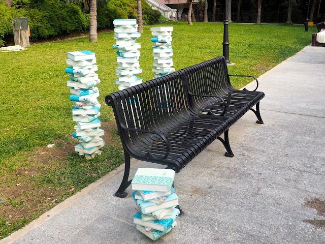 Art display of stacks of books around a park bench near Repulse Bay Beach, Hong Kong