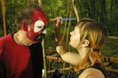 Applying makeup to horror clown