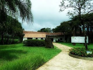 Área externa do Ecomuseu de Itaipu. Jardim, à esquerda. Painel explicativo,à direita. E prédio do museu ao fundo.