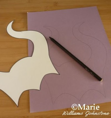 Horn template cut out from thick card and traced around onto purple cardstock with a pencil