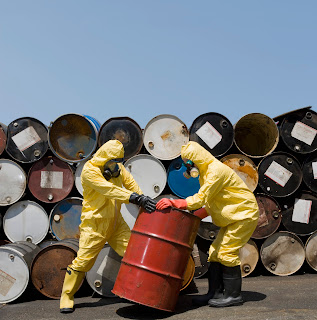 Men in hsz-mat suite work with barrels of toxic material.