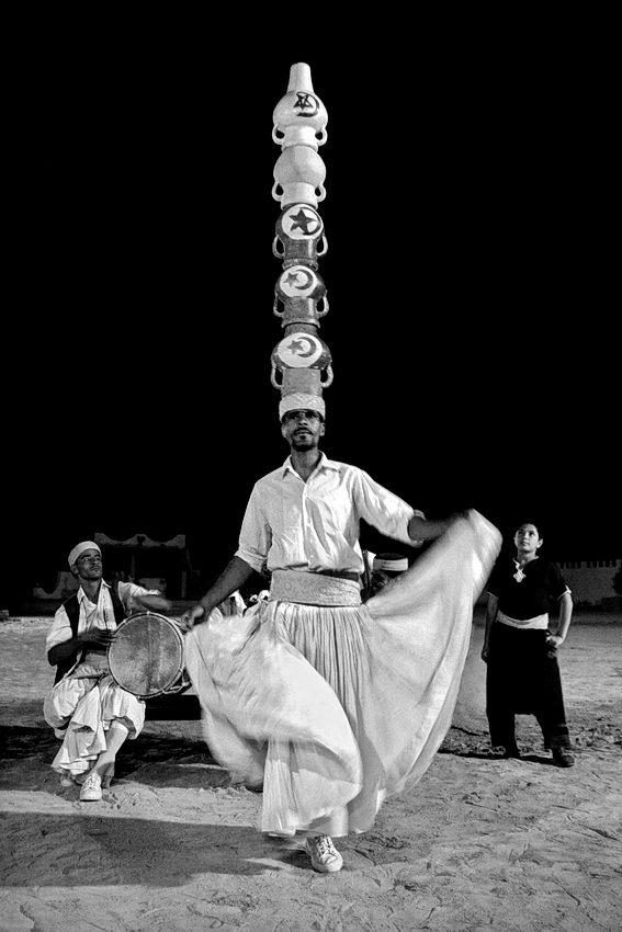 Foto num espectáculo nocturno com um homem a dançar com cinco bilhas cerâmicas na cabeça, um outro a tocar tambor e ainda outro a observar
