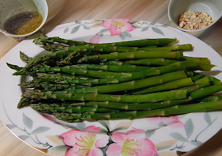 Plate of asparagus with dressing and almonds on side
