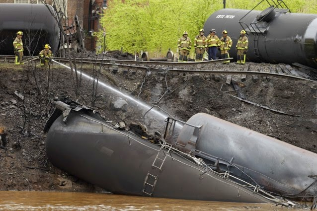 Firefighters and rescue workers work along the tracks where several CSX tanker cars carrying crude oil derailed and caught fire along the James River near downtown in Lynchburg, Va., Wednesday, April 30, 2014. (Credit: AP Photo/Steve Helber) Click to enlarge.