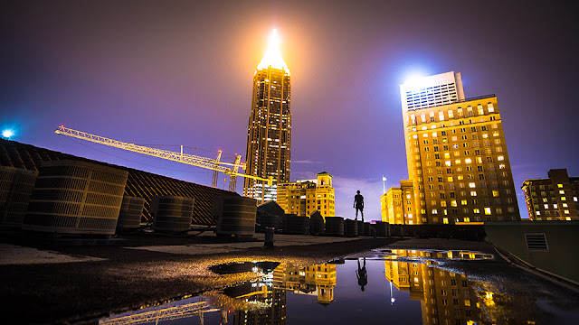 A lone warrior stands solemn at night while observing his pray: The tallest building in Atlanta.