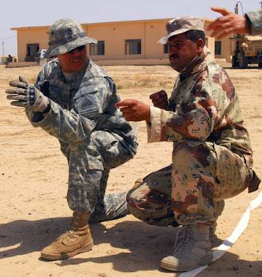 "A U.S. soldier, left, shows a Peshmerga fighter which way to face his ""weapon,"" during training near Kirkuk, Iraq, on June 14, 2010.(US Army)"