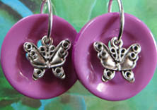 Bold drop dangle earrings have silver butterfly charms layered on big purple buttons