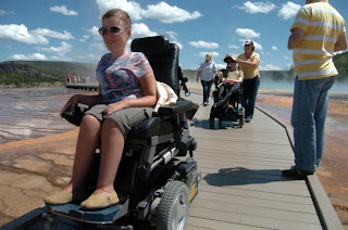 photo of two wheelchair users on wooden pathway with hot springs on their sides