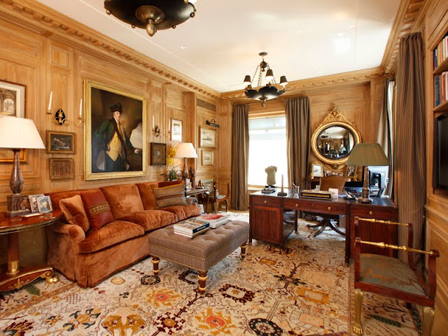 Home office with molded walls, large area rug, upholstered sofa, ottoman and chandelier