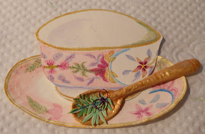 Handmade paper tea cup, really cute, over a matching plate with an embossed golden spoon with lavender twigs tied with a purple bow on it