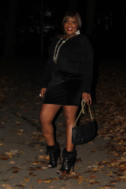 Dressed-in-all-black-like-the-omen- warm-and-fuzzy-black-cropped-sweater-worn-with-black-velvet-mini-skirt-and-fur-trimmed-black-booties-with-chain-detailed-black-clutch