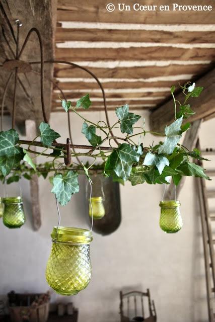 Décorer une armature en fer forgé de lumignons en verre et de quelques branches de lierre pour créer un lustre festif