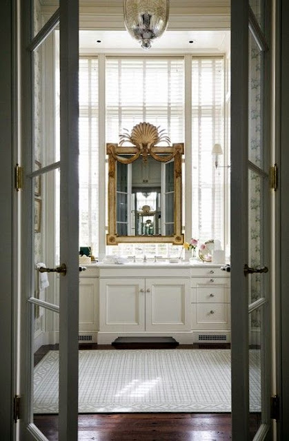 white master bathroom with dark hard wood floors gold framed gilt mirror