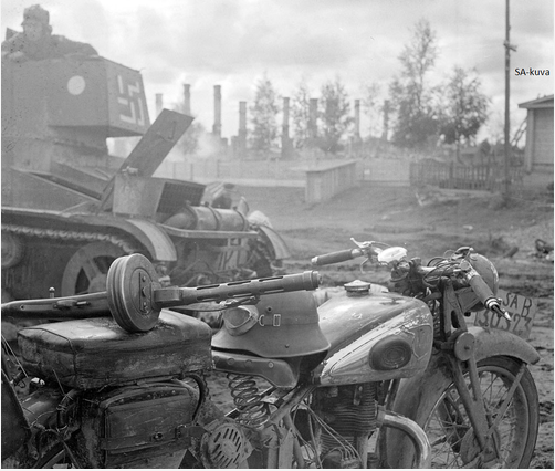 Finnish motorcycle couriers bike and his Suomi submachine-gun M-31 and on the background T-26 where its commander is out of the hatch. Somewhere in the eastern front 1941-1944.PNG