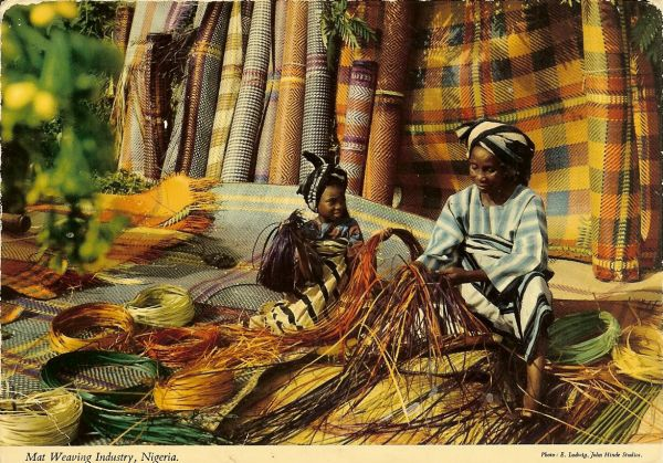 woman and child in traditional dress weaving mats