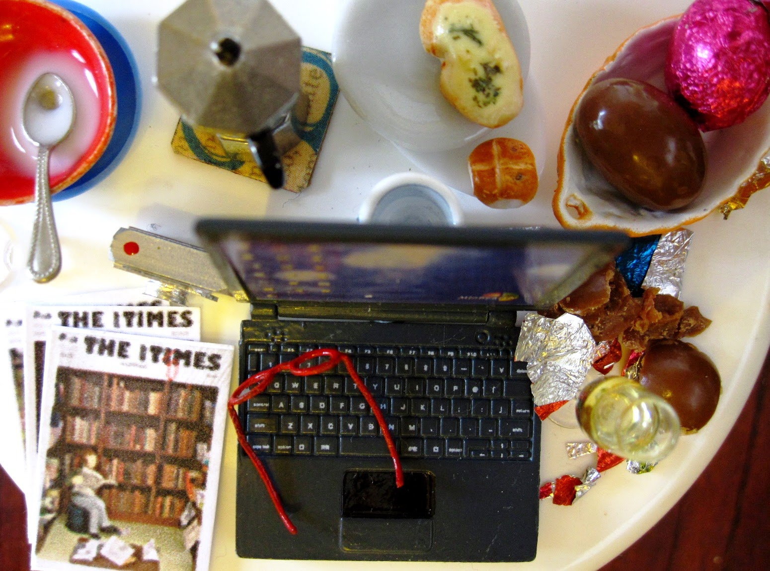 Modern dolls' house miniature round table with a laptop computer, digital camera, reading glasses, back issues of The tiny Times, and plates and bowls and cups containing half-eaten pieces of food, including Easter eggs.