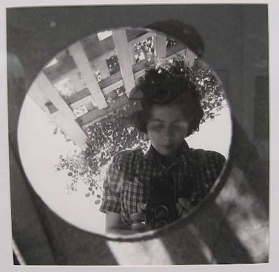 Young women with tousled dark hair photographing herself in a round mirror, set on the ground as if it were a hole in the ground