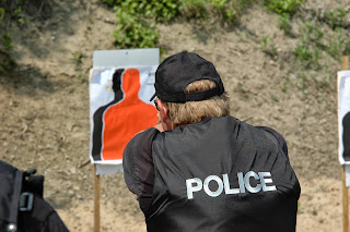 Police officer fires on a target at a shooting range.