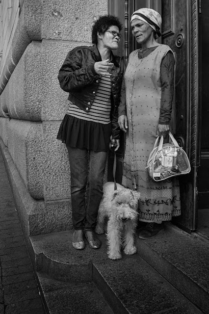 Two women stand in a doorway with a dog in this street photograph