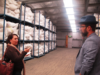 Woman and man talking in a large shed, in front of pallet racks holding large bags of clothing.