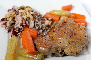 Turkey thigh accompanied by braised carrots and celery, and a mound of cranberry wild rice.