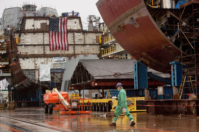 An employee walks a yard filled with partial ship assemblies at Bath Iron Works