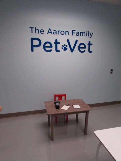 pet vet, table, chair, rotary dial phone, paper, pens