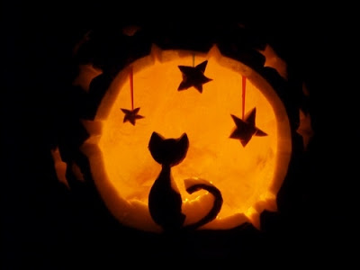 Carved Jack-O-Lantern with cat and stars.