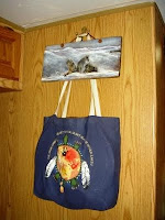 Drum Bag hanging under painting of wolves on barn wood.