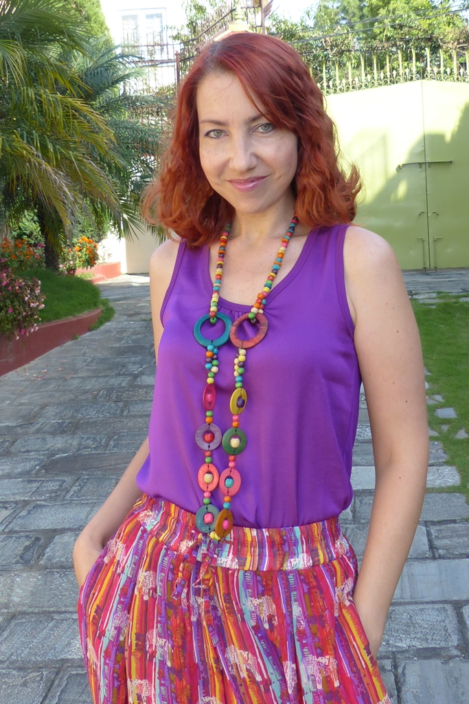 Purple top worn with gypsy palazzo pants and multi-coloured wooden necklace