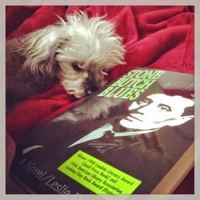Murchie lays atop a red bedspread, his head resting dejectedly atop his paws. In front of him is a paperback copy of Stone Butch Blues. Its cover features a stark black and white photocopy-style image of a pale, short-haired person wearing a jacket and tie.