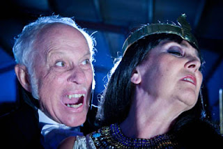 John Carson as Older Gentleman, a smooth, aristocratic predator and Caroline Munro as the Evil Priestess