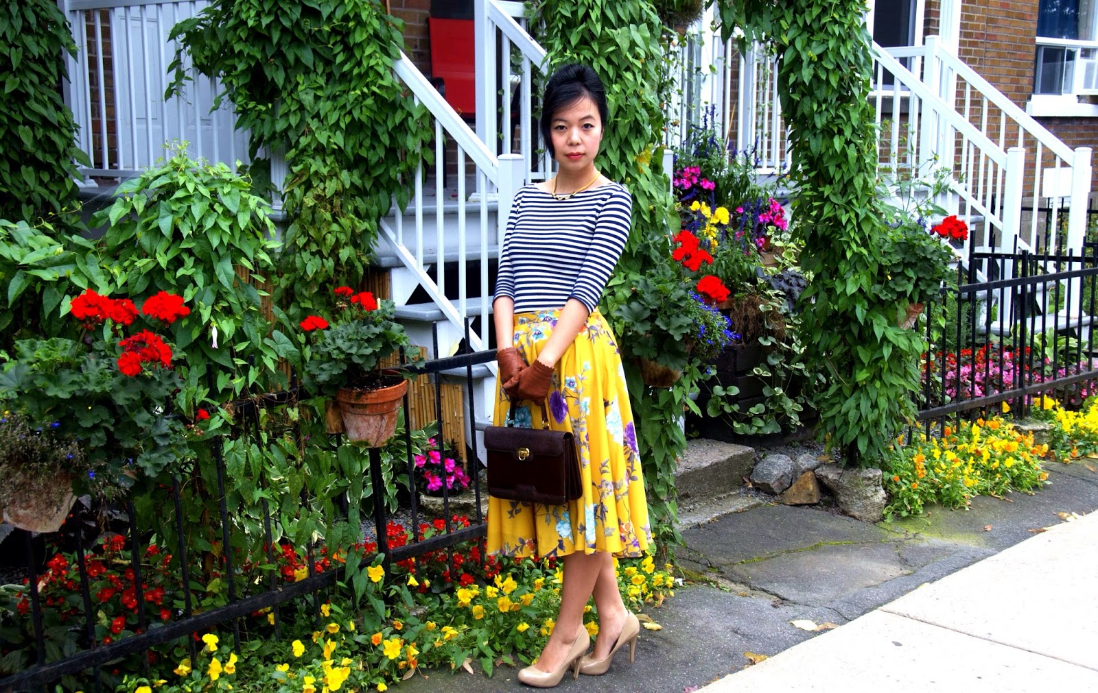 yellow floral skirt leather gloves striped shirt nude pumps heels brown handbag flowers