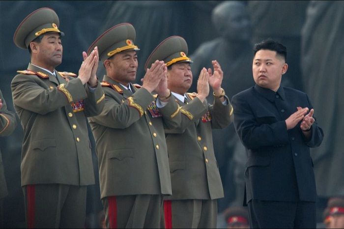 A trio of North Korean army officers clapping with Kim Jong-un