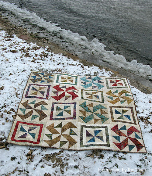 Spinners quilt lying on the ground by the river