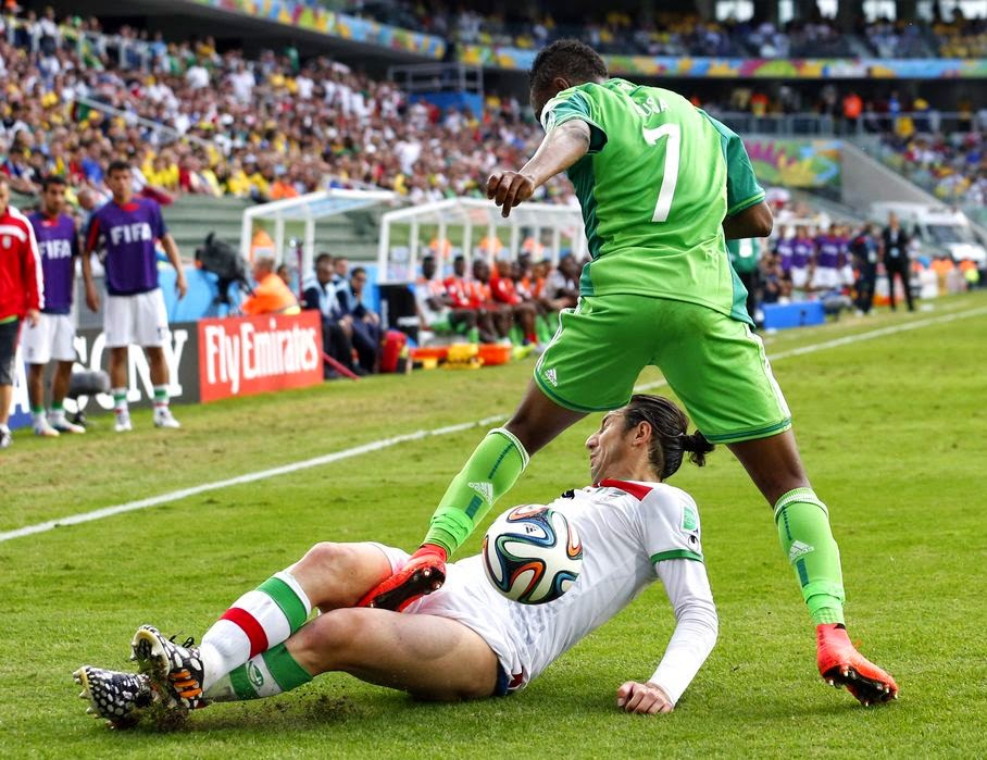 Iran's Andranik Teymourian slides under Nigeria's Ahmed Musa to take the ball away during the group F World Cup soccer match between Iran and Nigeria at the Arena da Baixada in Curitiba, Brazil, Monday, June 16, 2014.