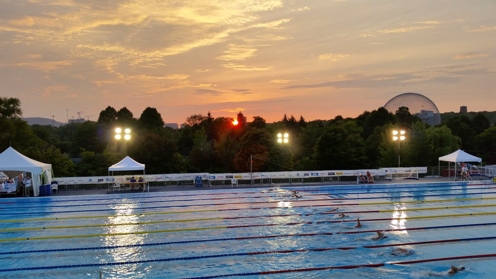 The Temporary Pool at sunset during the first day of competition.  800m freestyle heats continued well into the evening.  Note the geodesic dome (now a biosphere) on the right which was constructed during the 1967 world Expo in Montreal