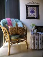 Bamboe leuningstoel en kleine tafel. Een korf met haaknaalden zit op de stoel.  Een kopje thee zit op de tafel.