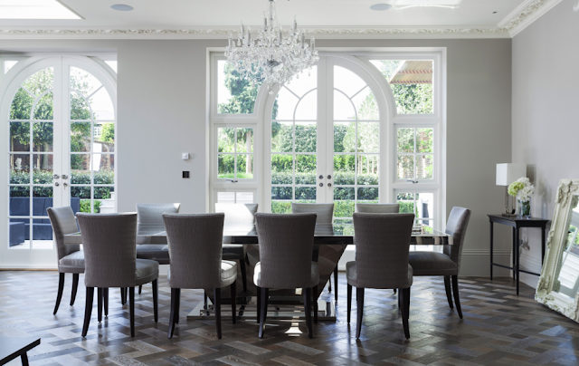 Dining room in a suburban London home with carved crown moulding, ceiling medallions, parquet wood floors, crystal chandelier and arched french doors overlooking a manicured backyard