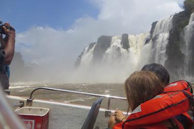 Foto mostrando as cataratas de Foz do Iguaçu, visto de dentro de uma embarcação, próximo à queda d'água.