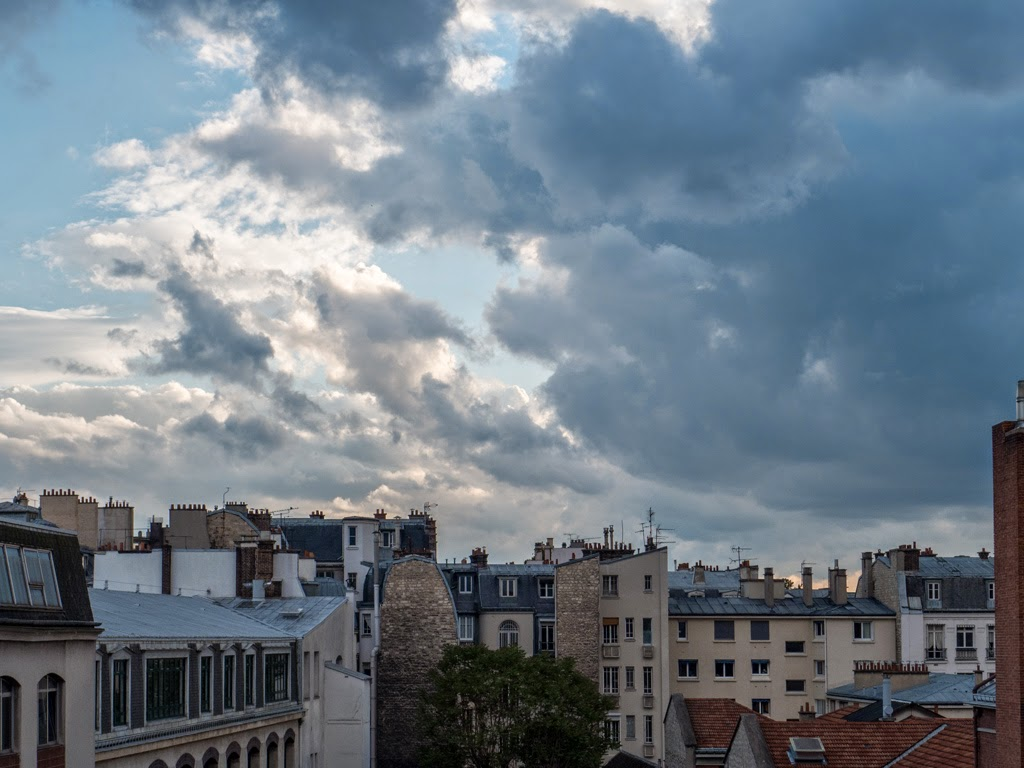 Paris France view from window rooftops clouds