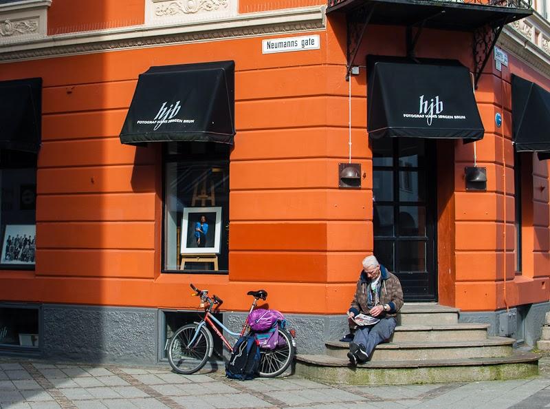Old man reading outside a café