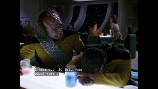 "Worf leans over Geordi at the bar of Ten-Forward, saying ""I have much to teach you about women."""