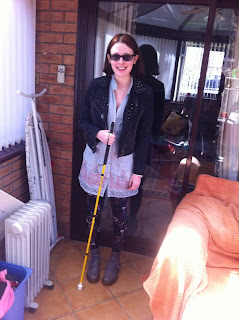 A picture of me wearing light purple doc marten lace up boots, a dress, brightly patterned leggings and a denim jacket. I am also holding a bright yellow cane.