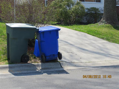 Trash can and paper recycling cart set lawn next to driveway.